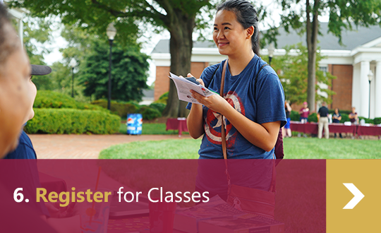 6. Register for Classes - Female student visits advising table at orientation.