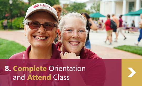 8. Complete Orientation and Attend Class - 2 female Mitchell employees hug and smile into the camera during orientation.