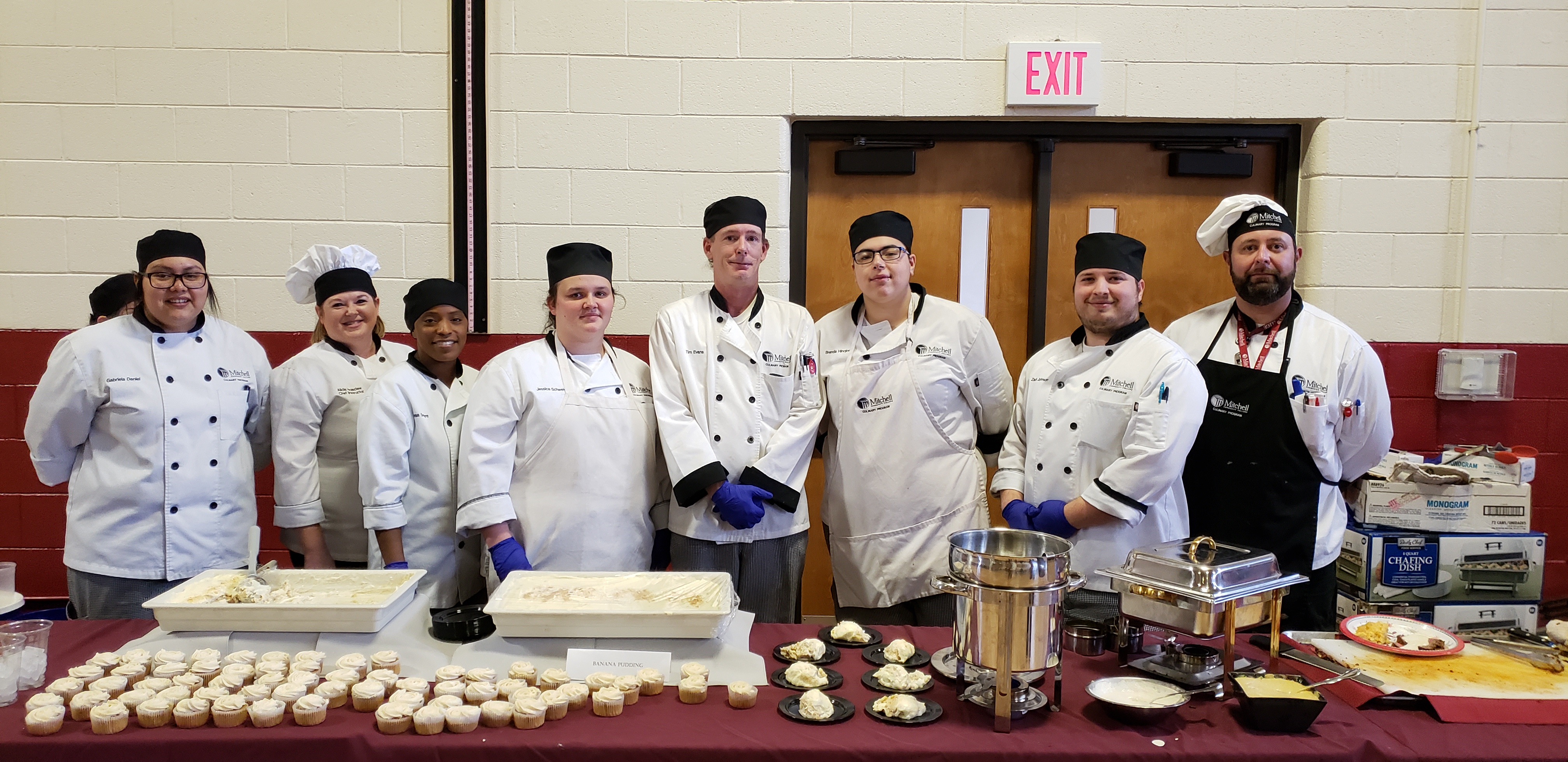 Mitchell Culinary Arts students pose with instructors Chef Bob Williams and Chef Alicia Holesclaw at Thursday's luncheon