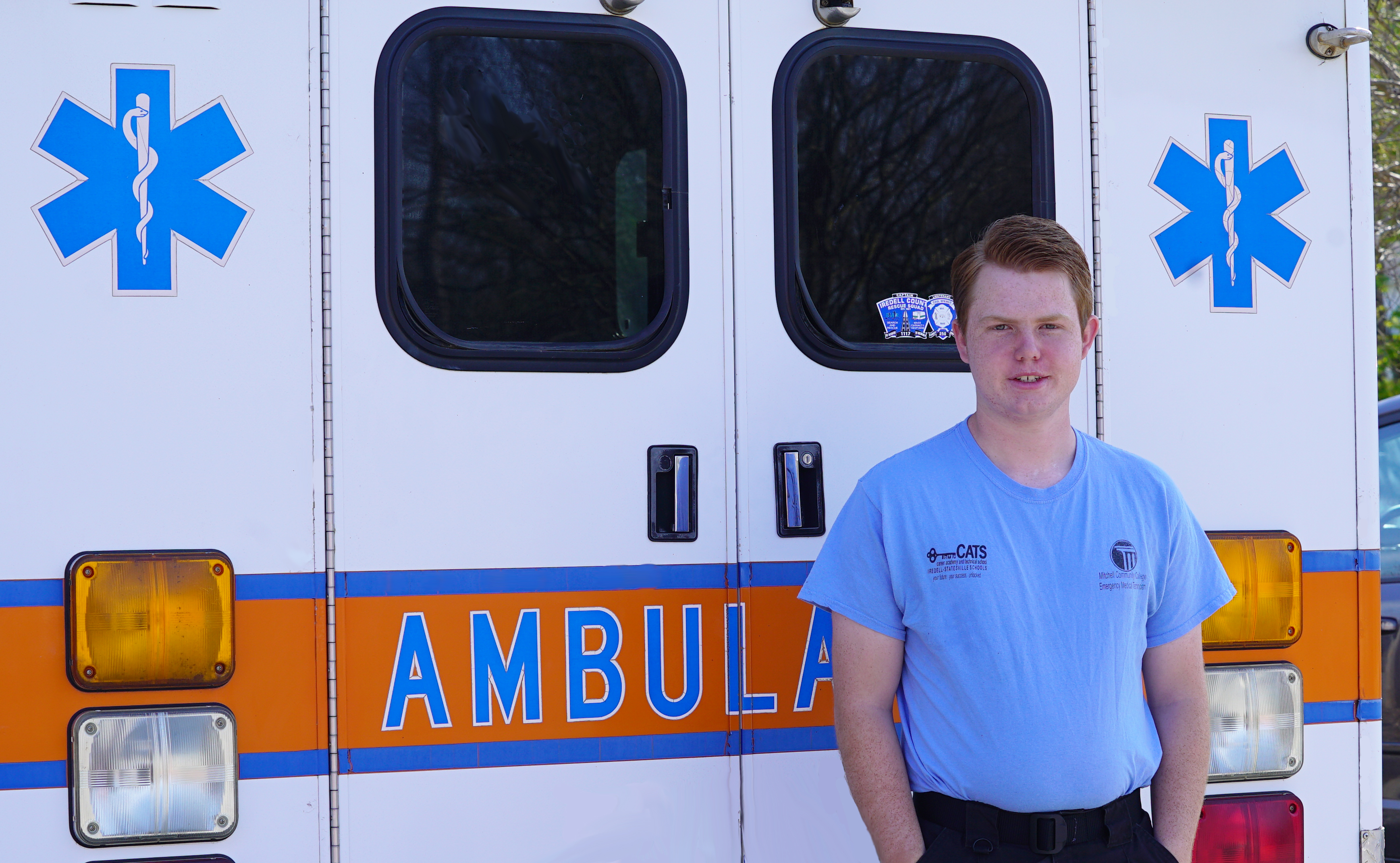 Luke Swing stands in front of an ambulance.