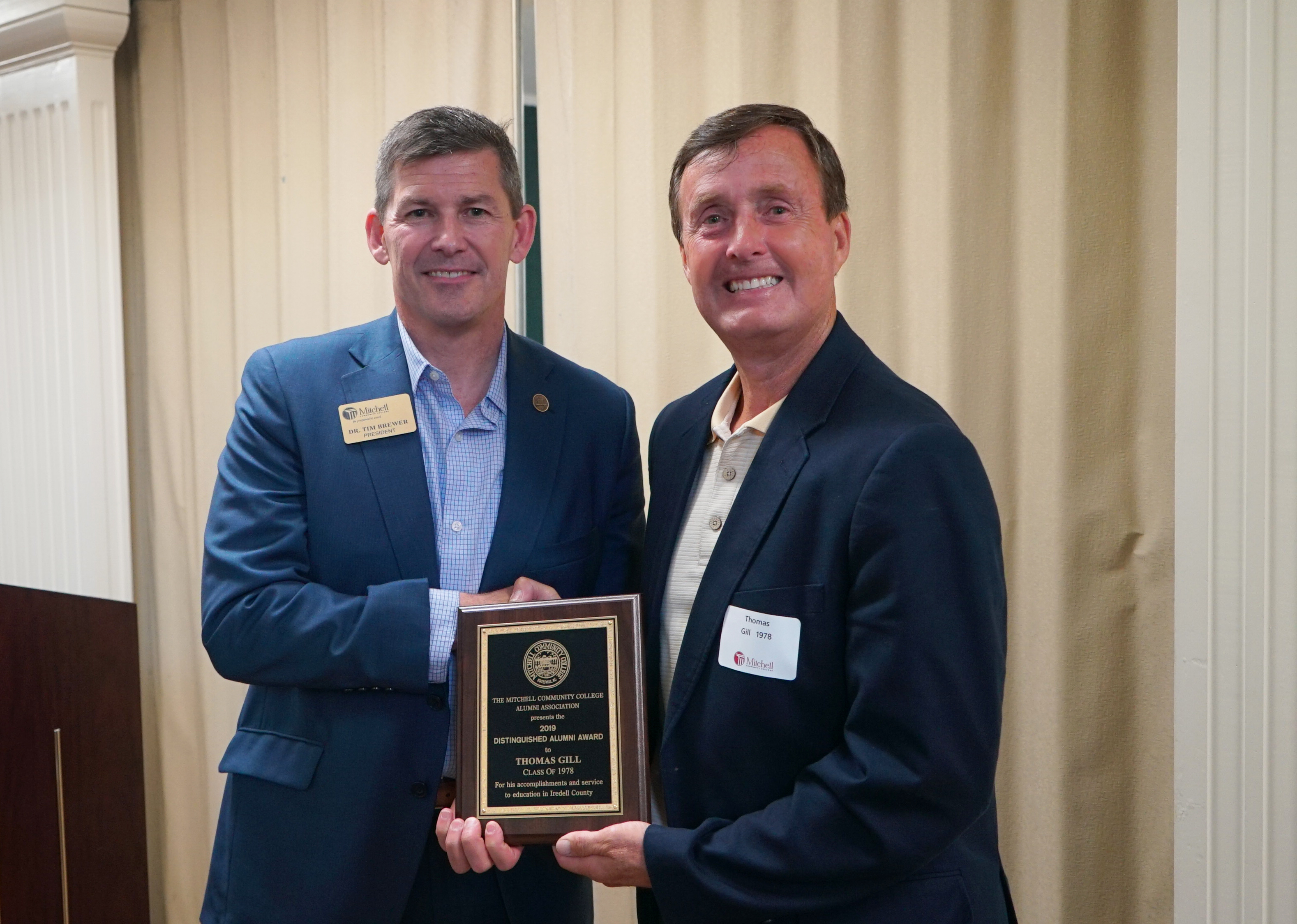 Tom Gill accepting plaque from Dr. Brewer