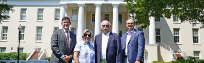 (L-R) Dr. Tim Brewer, Carol Childress, Frank Childress, and James Hogan stand in front of Mitchell's historic Main Building on the Statesville Campus.