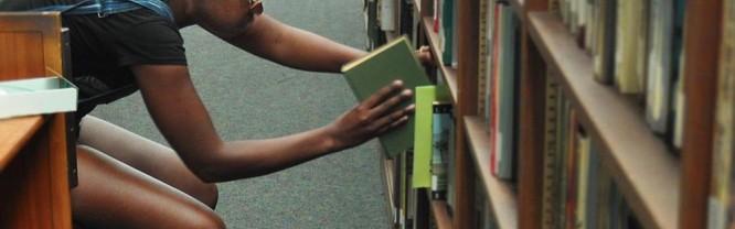 Student Ashley Brown shelves books in Huskins Library.