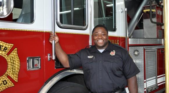 A firefighter beside a fire truck