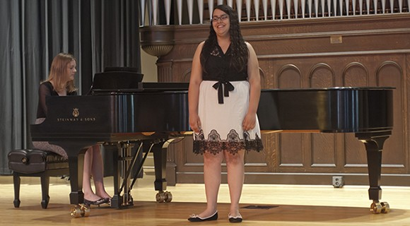A vocalist performs to piano accompaniment.