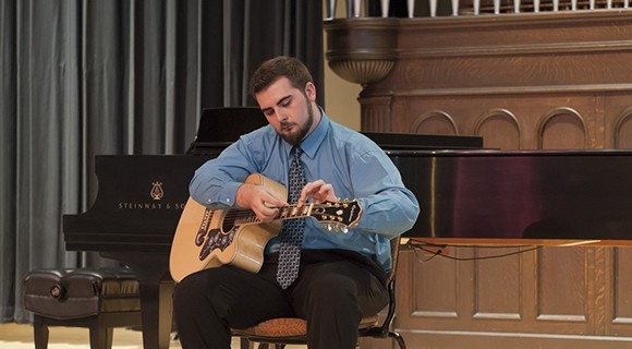 Guitarist prepares to perform on the Shearer Hall stage.
