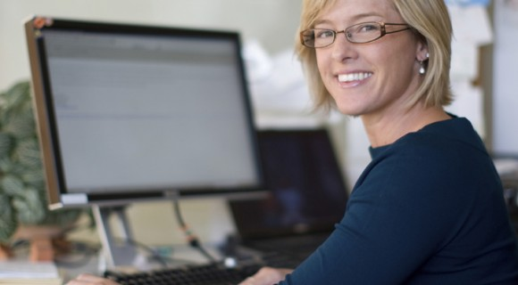 Woman at keyboard, looking back over left shoulder smiling into the camera