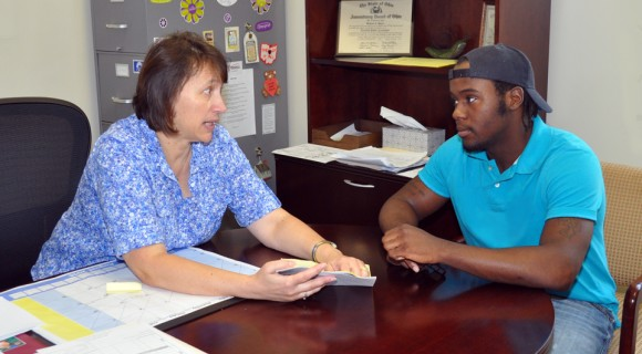 A student meets with a counselor about transcripts