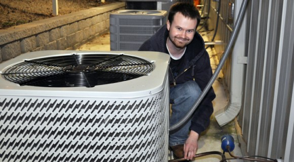 HVAC tech works on heating and cooling unit