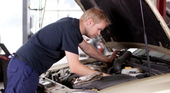 Mechanic works on car engine