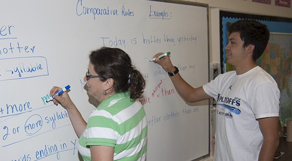 Students practice a grammar lesson on the whiteboard.