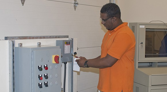 An industrial maintenance student utilizes lock-out, tag-out procedures.