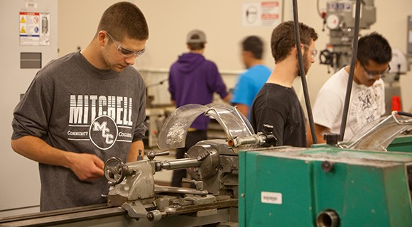 Students work at lathes in machining lab.