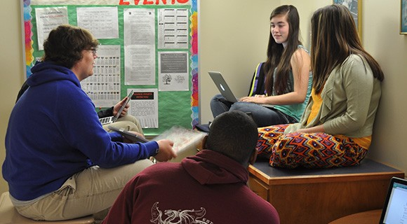 CCTL students huddle with laptops to work on an assignment.