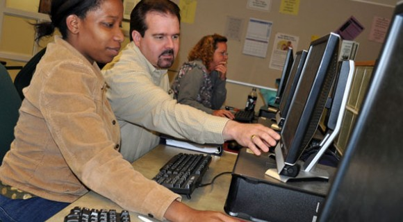 Instructor helps students in computer class