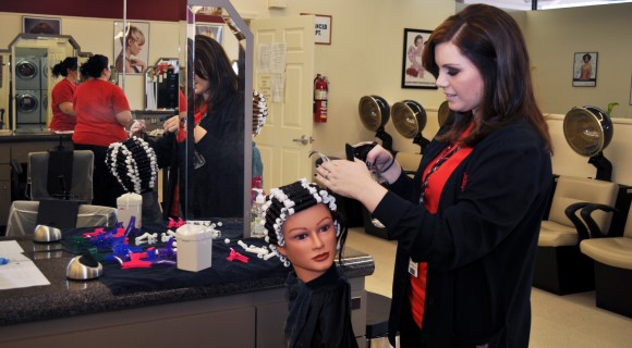 Cosmetology student practices rolling hair.