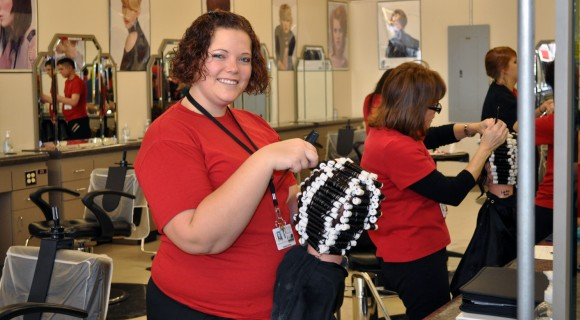 Cosmetology student rolls a mannequin's hair.