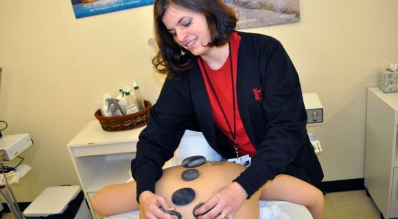 Student places hot stones during a spa treatment