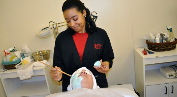 Cosmetology student paints on a mask during a facial.