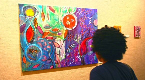 A young gallery visitor admires the bright colors in the painting.
