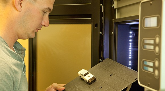 Student pulls 3-D printer project out of the printer.