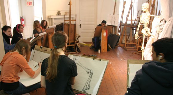 Art students draw a skeleton in art class.  Mitchell Community College Art Department