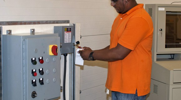 An Electrical Systems Student uses lock-out, tag-out