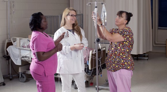 Nursing students learn to hang IV bags, medical office assistant