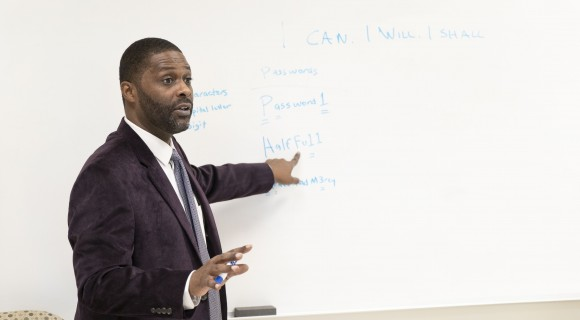 An instructor points at a whiteboard in a classroom.