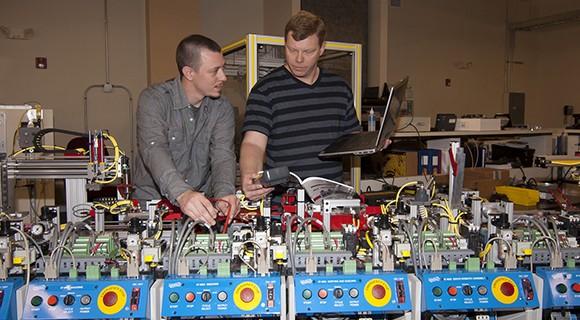 Students work with equipment controls utilizing mechatronics training.