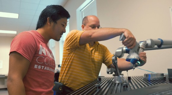 Engineering student and instructor use a scanning tool