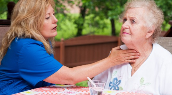 Speech-language pathology assistant checks a patients neck.