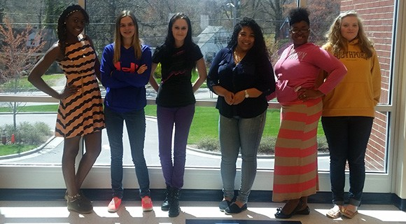VPAC students line up for a photo in front of the window.