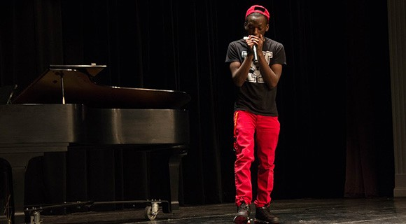 A VPAC student plays harmonica on stage.