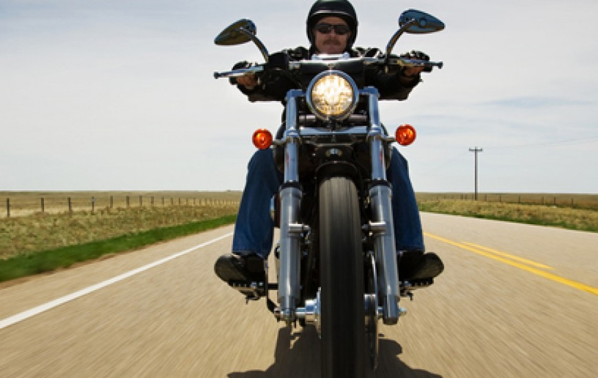 motorcyclist riding down an empty highway in the country