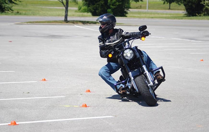 motorcyclist going around orange cones in an empty parking lot