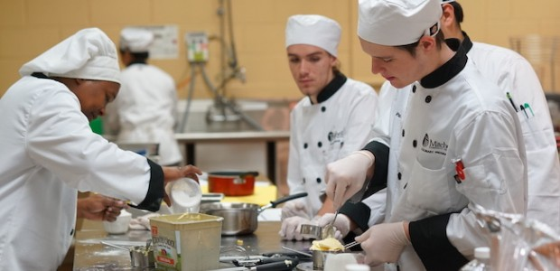 Group of culinary students preparing food in kitchen.