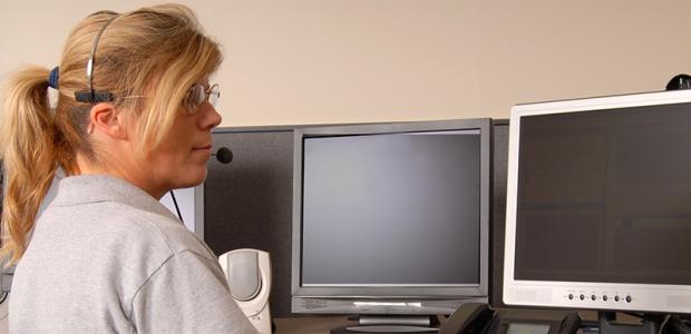 Telecommunicator sits at a desk