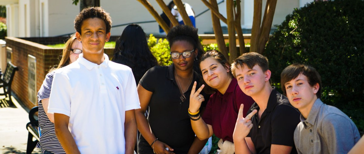 Five Students pose for picture in front of the Montgomery Student Union building