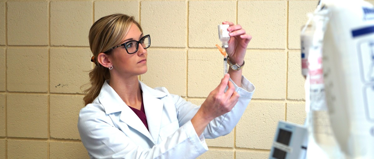 A Nursing student measures a medication.