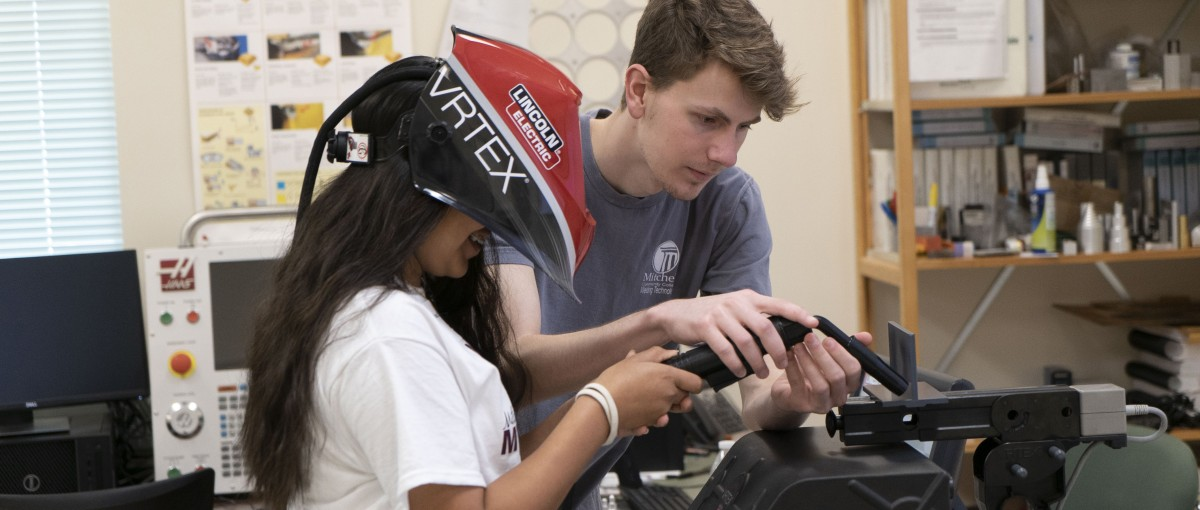 A Welding student instructs a future Mitchell student on a welding simulation machine.