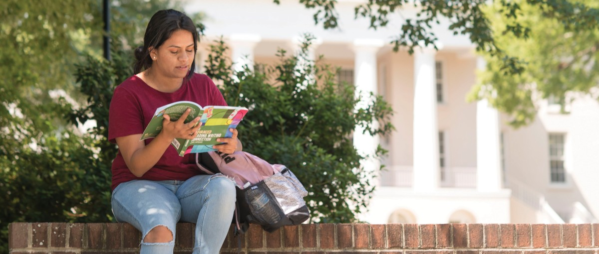 A female student reads a book on the Statesville Campus circle.
