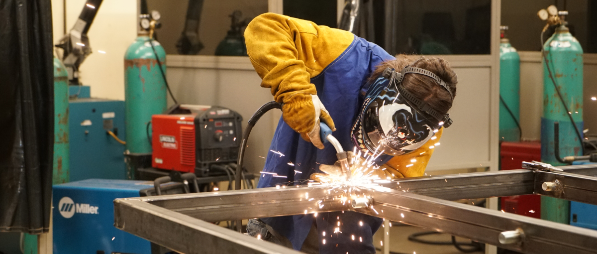 A welding student works in the lab.
