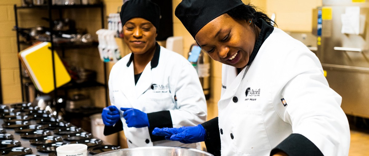 Two smiling culinary students work on preparing a meal in the kitchen