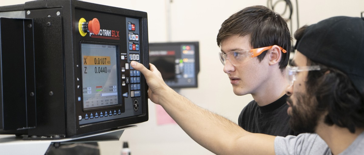 Two smiling students working on machining equipment