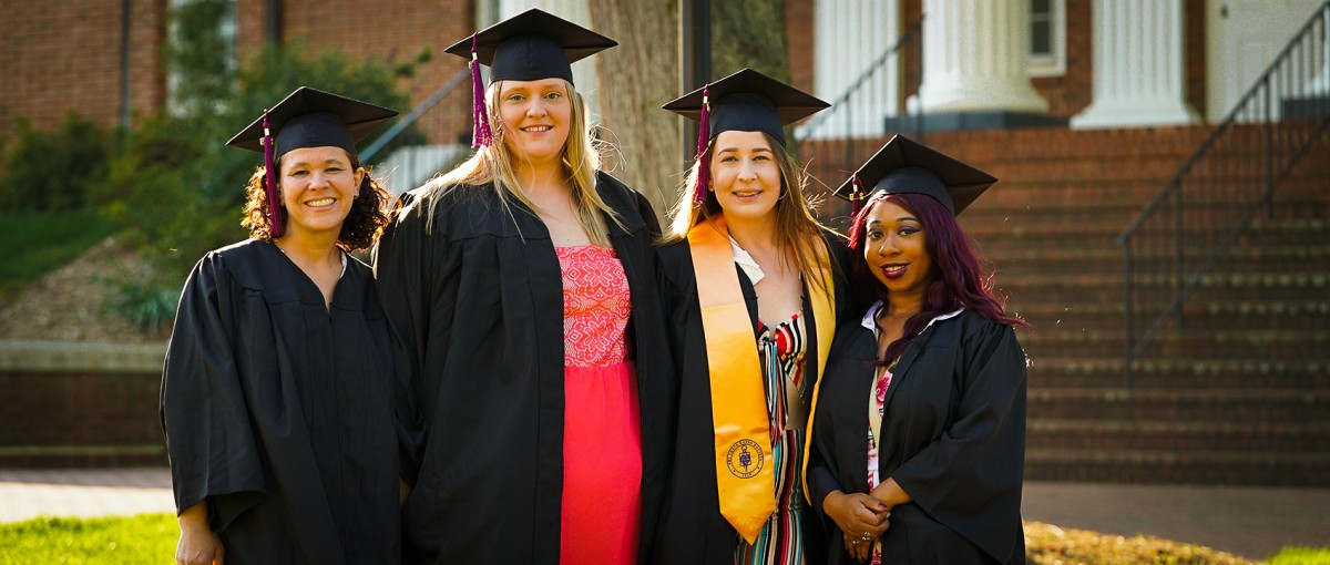 4 female students pose in their cap and gown.