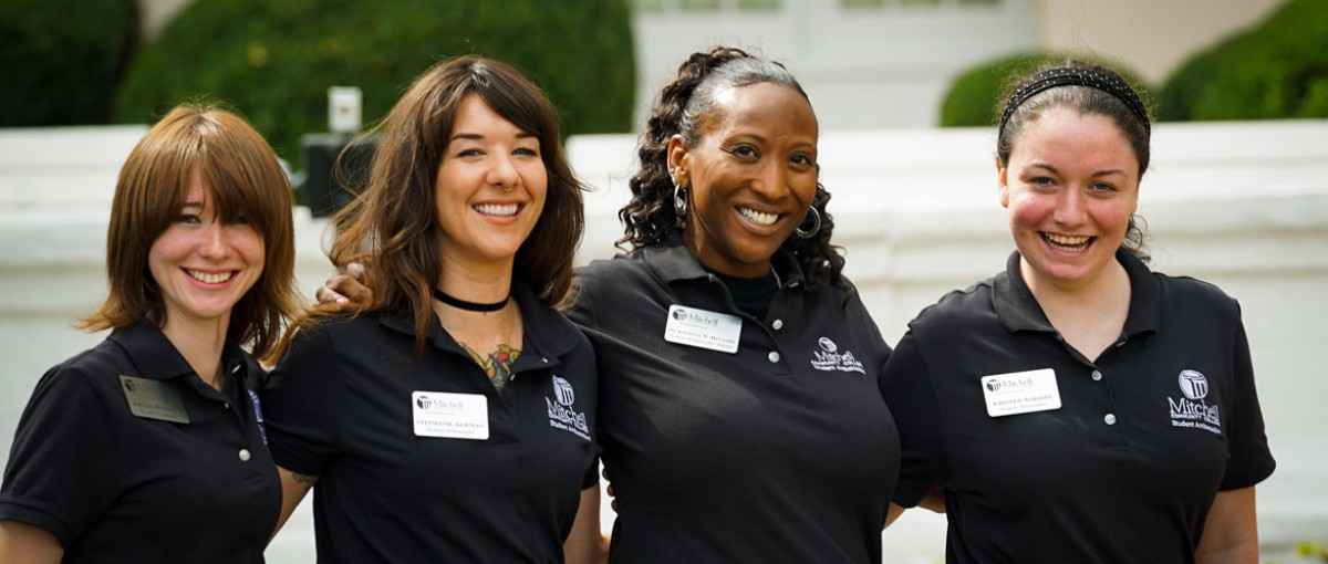 four ladies smiling and posing with arms wrapped around each other, standing in front of Main Building on the Statesville Campus