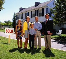 Family standing in front of a house marked sold