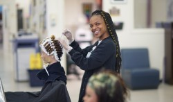 Cosmetology student smiles into the camera while putting curlers in the hair of a mannequin