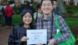A female graduate stands side-by-side with a male friend while holding her diploma.